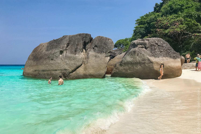 Grote rotsformaties in de blauwe zee en op het witte strand