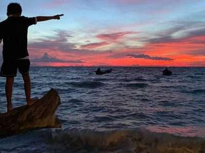 Een Jongen Wijst Naar De Zonsondergang Op Koh Tao