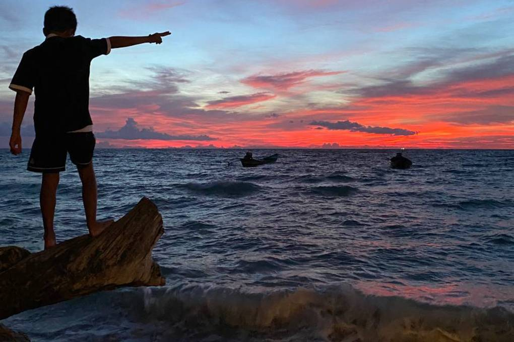 A boy points to the sunset on Koh Tao