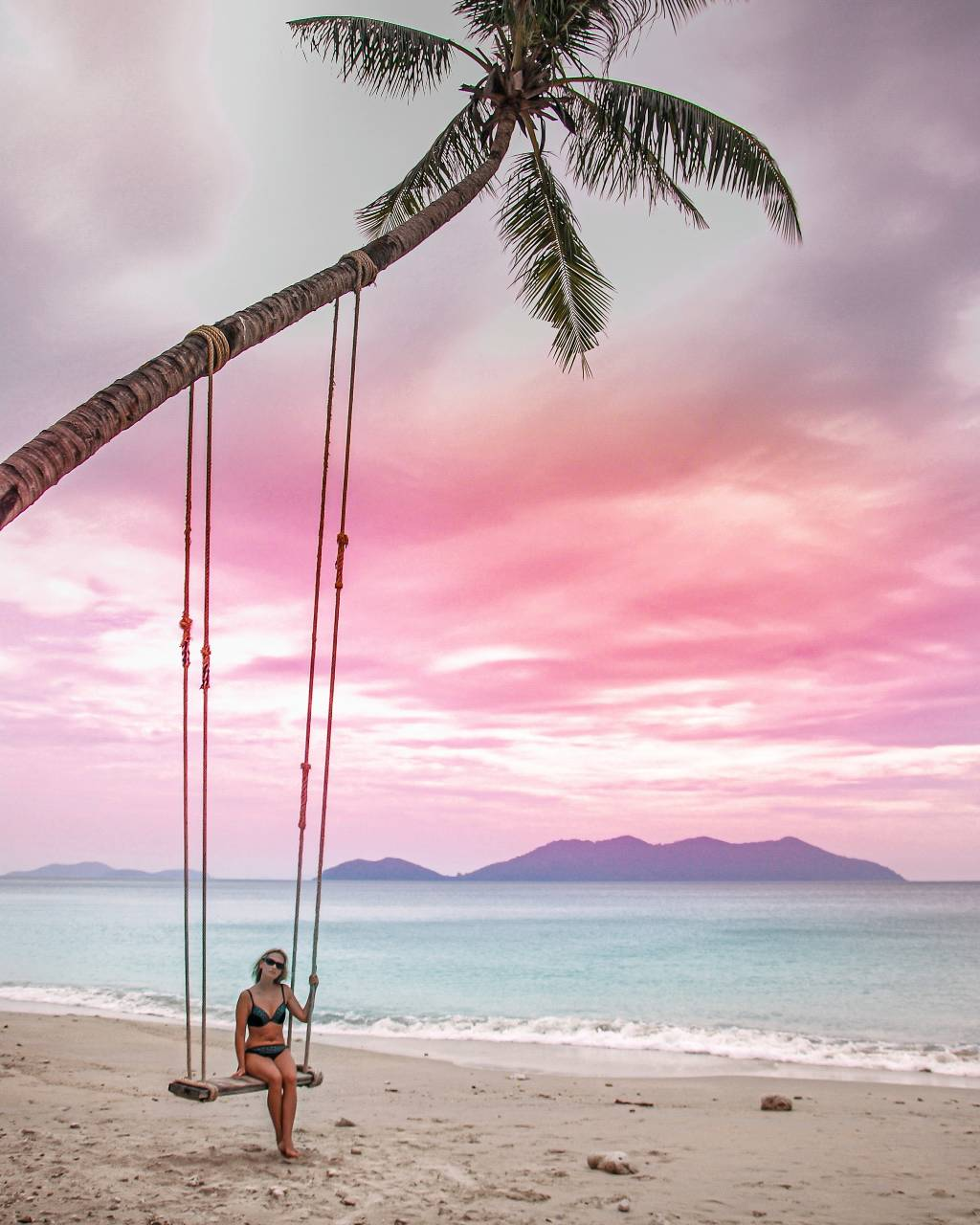 Woman on swing at sunset on Koh Chang in Thailand