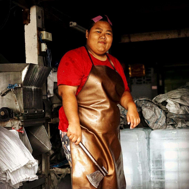 Ice lady chopping ice cubes in Bangkok, Thailand