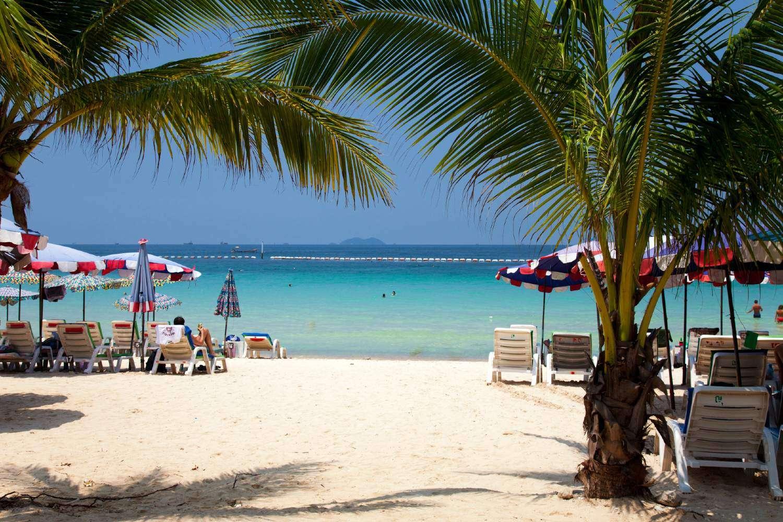 Palmbomen en ligbedjes op het witte strand van Koh Larn