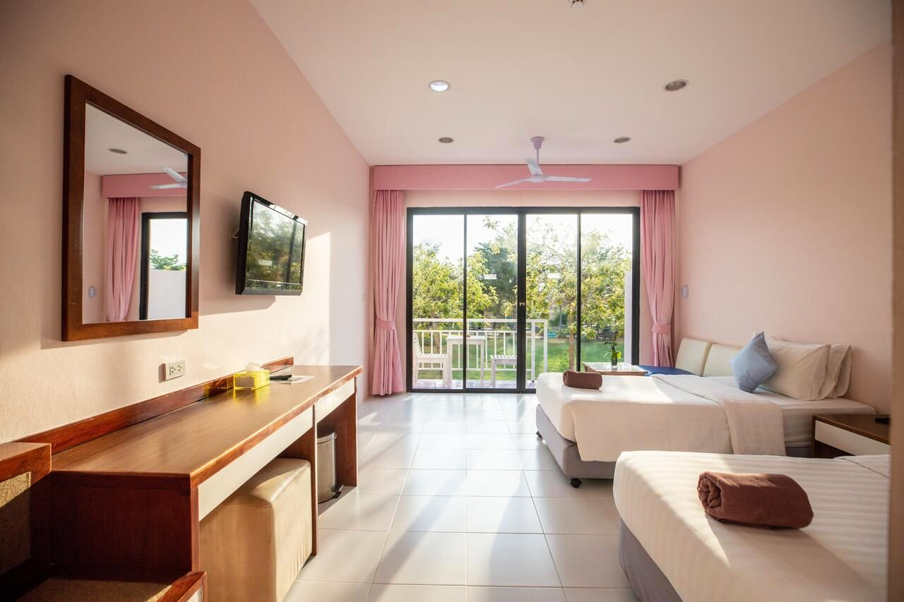 Slaapkamer met 3 bedden en balkon Xanadu Beach Resort.