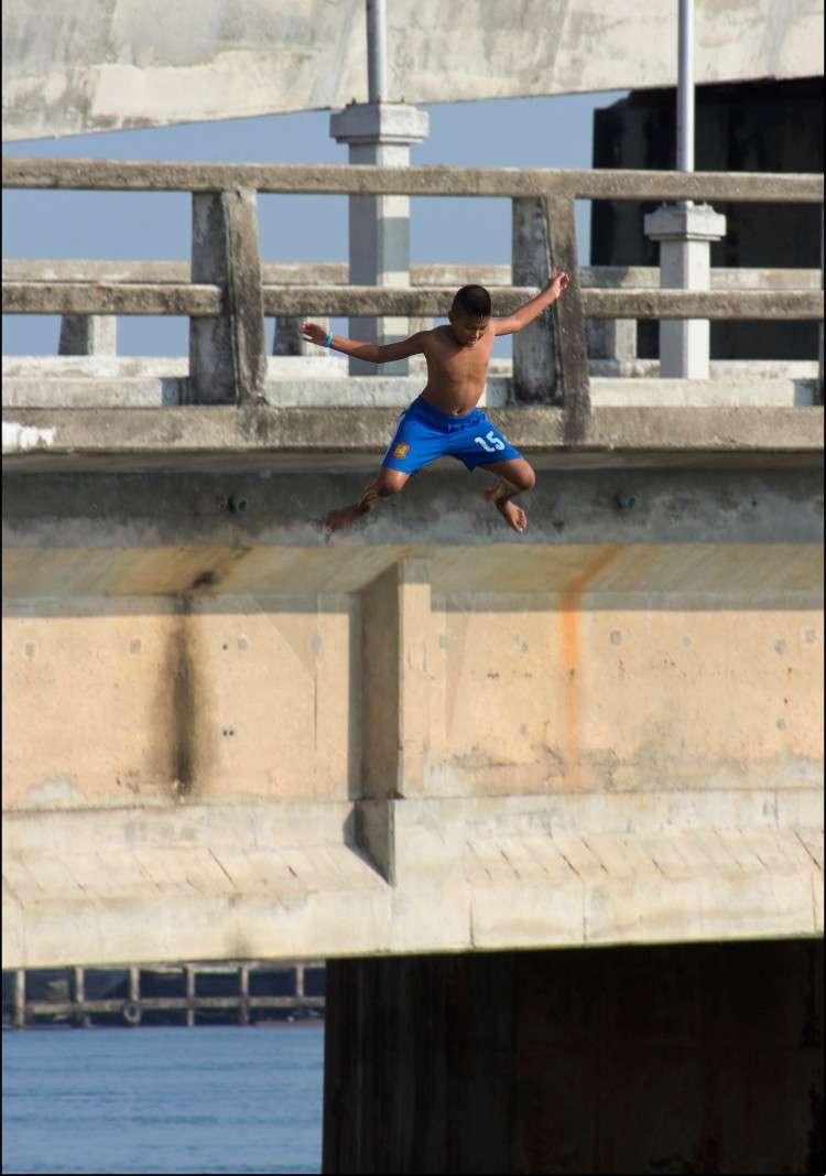 Kind die voor de fun van de Sarasin brug springt