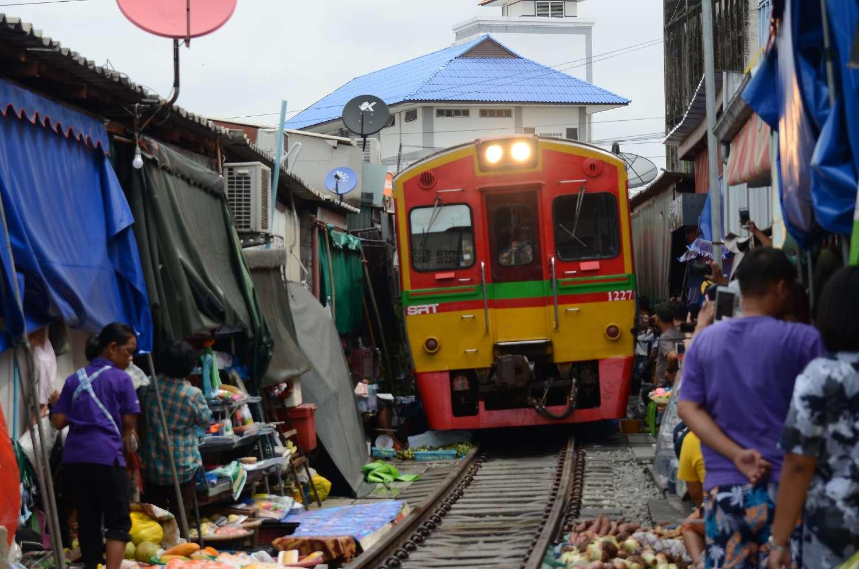 Trein die vlak langs demarktstalletjes rijdt van de Maeklong Railway Market in de buurt van Bangkok, Thailand