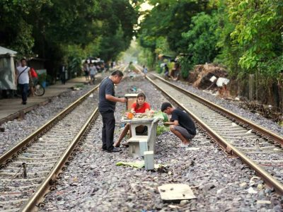 Having Dinner Between Two Railroad Lines In Bangkok