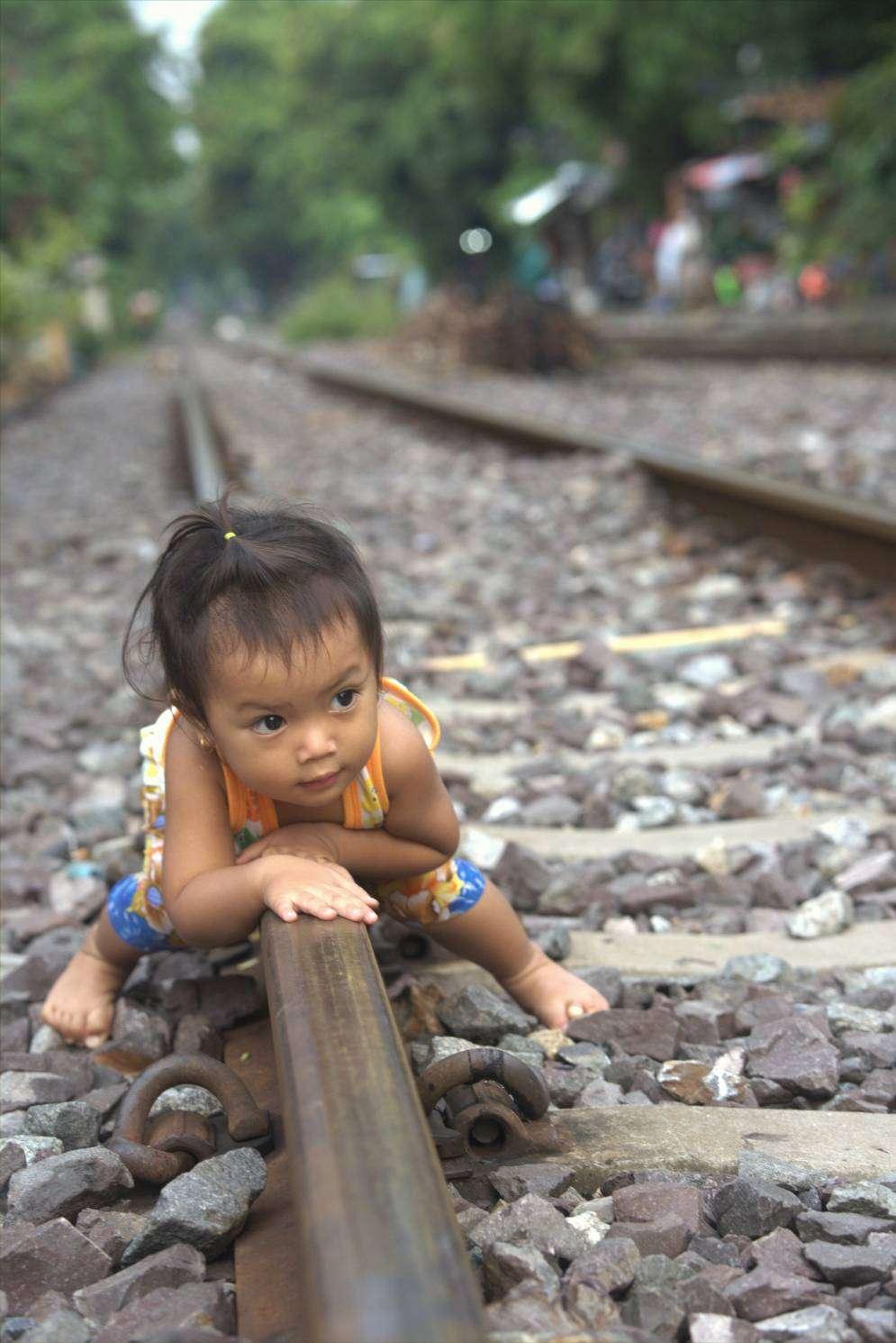 Kindje aan het spelen op een spoorlijn in Bangkok