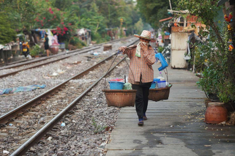 Een vrouw uit Isarn gaat terug naar huis langs de spoorlijn nadat ze de dag heeft doorgebracht met het verkopen van somtam