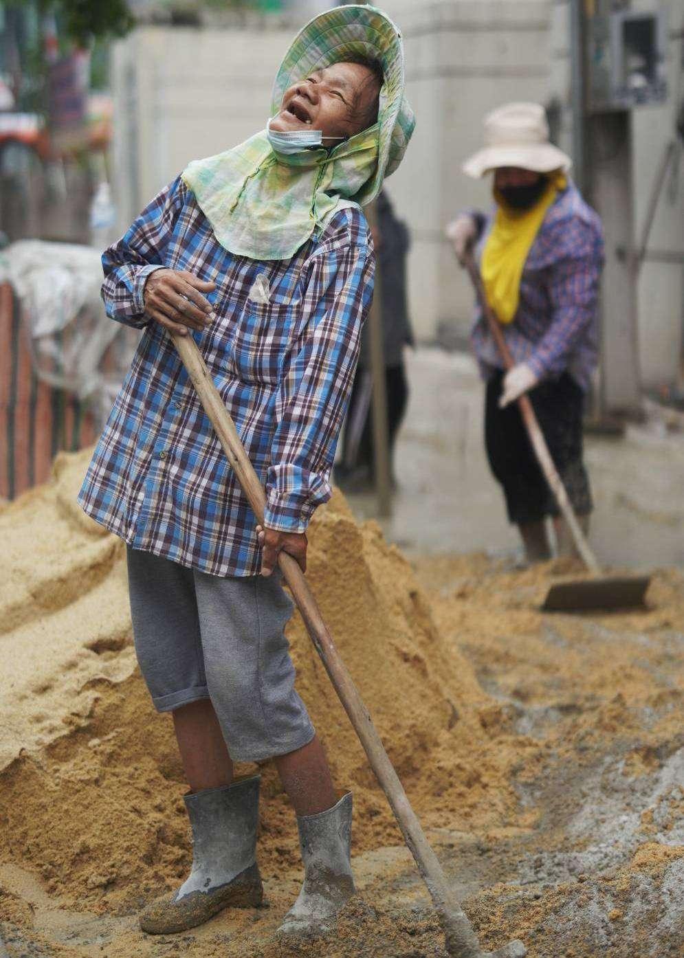 Vrouw die op straat aan het werk is die in een deuk ligt