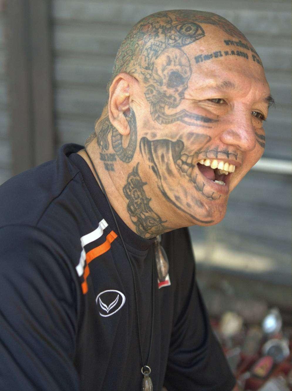 Lachende man met tattoos op zijn hoofd in Bangkok