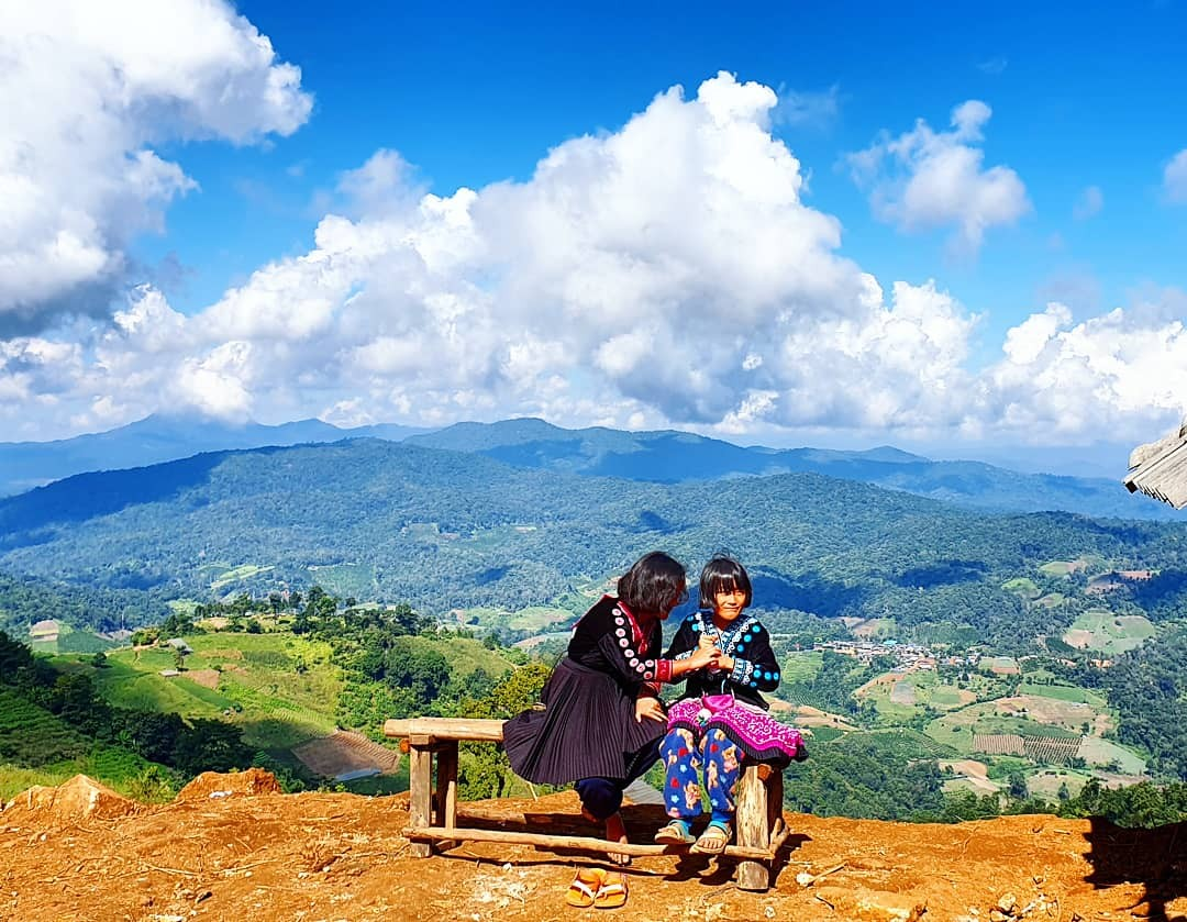 Twee Hmong meisjes in hun traditionele kledij genieten van de zon in de koude ochtend op Mon Cham, Chiang Mai, Thailand