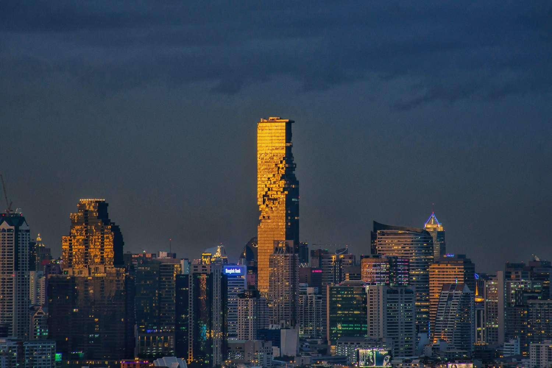 Door de zon goud verlichtte King Power MahaNakhon in Bangkok