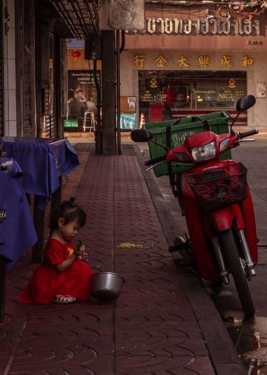 Meisje spelt met een pot op straat in Chinatown, Bangkok
