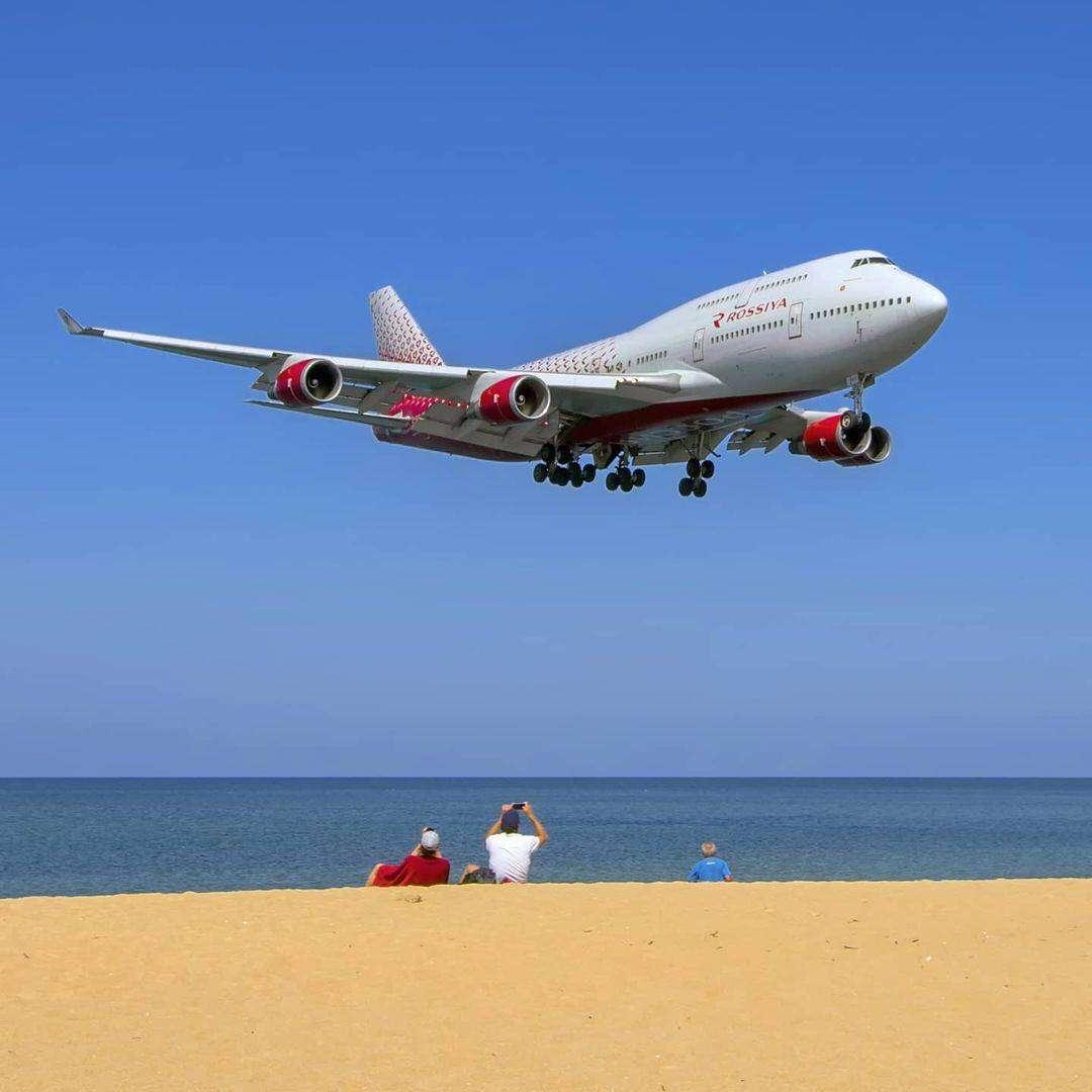 Vliegtuig laag boven Mai Khao Beach op Phuket