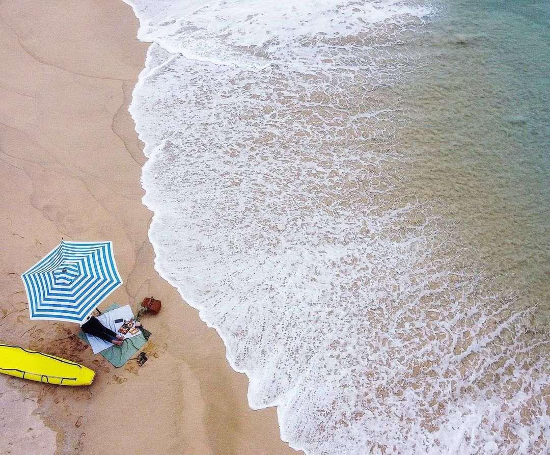 Parasol met surfboard ernaast op Nai Thon Beach