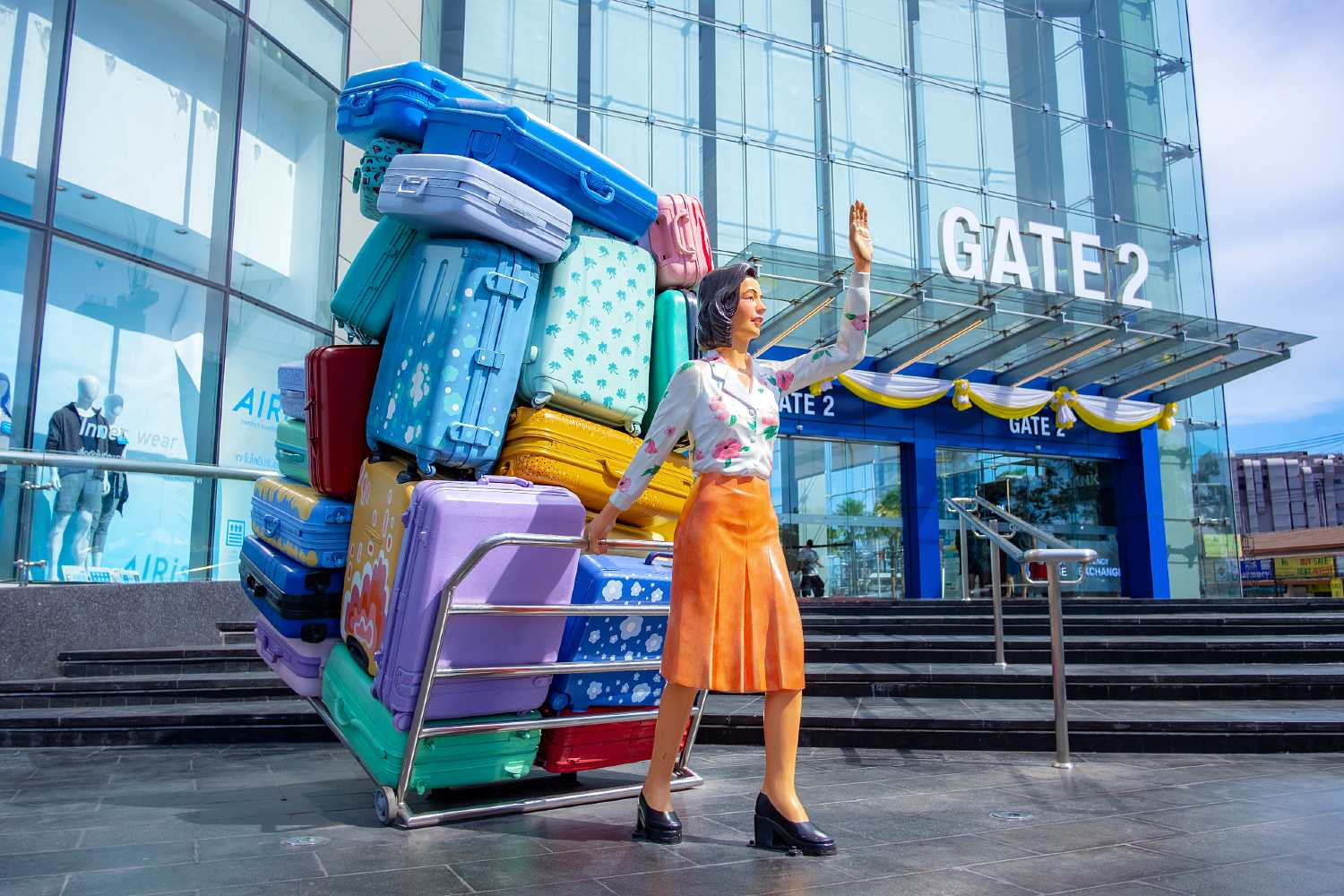 Image of woman with cart loaded with suitcases in front of mall