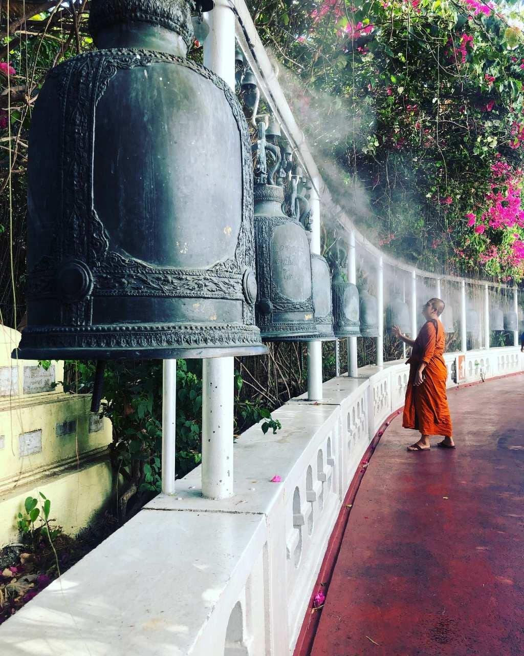 Boeddhistische monnik bij grote bellen op de Wat Saket (Golden Mount tempel) in Bangkok, Thailand