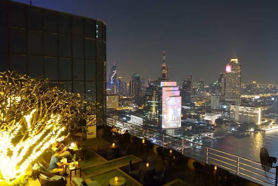 Verlichte boom en het uitzicht vanaf de ThreeSixty Jazz Lounge and Rooftop Bar van het Millennium Hilton Bangkok