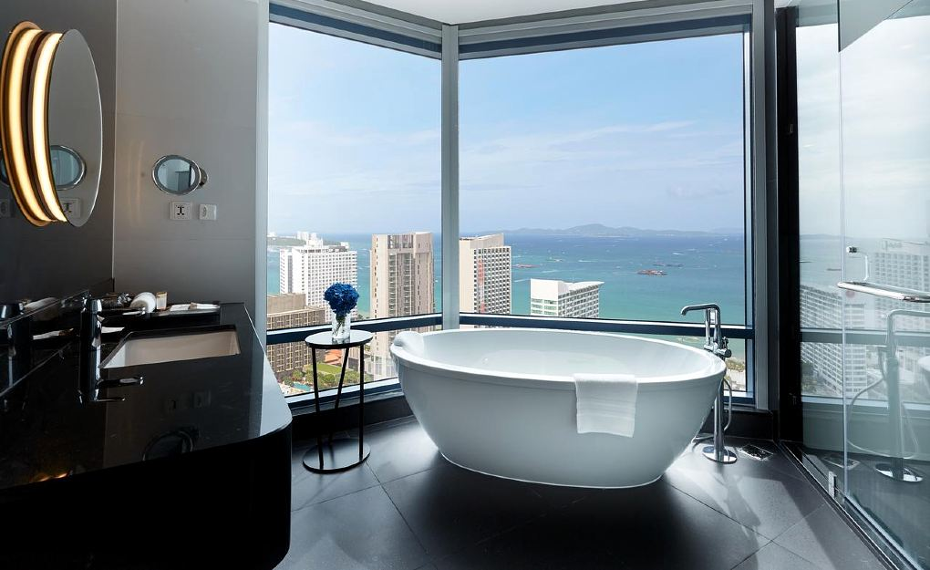 bathtub in bathing room with large glass wall overlooking Pattaya at Grande Centerpoint