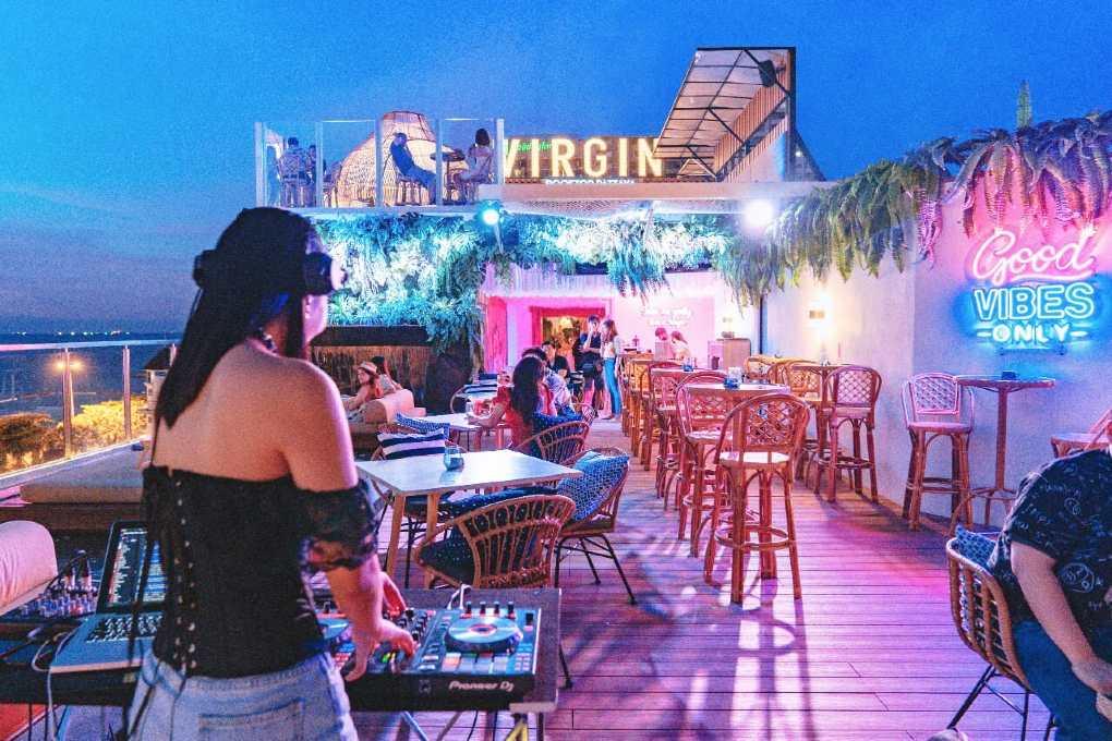 Female DJ behind turntables at Virgin Rooftop et views of the sea