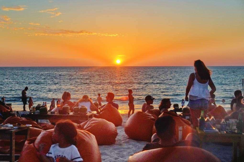 Relax met een groep mensen zonsondergang op Layan Beach bij Hugo Hut kijken