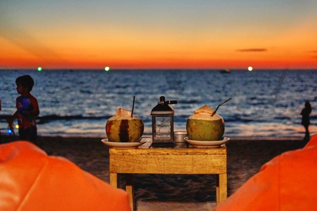 Kokosnoten drinken terwijl je de zon onder ziet gaan boven Layan Beach op Phuket bij Hugo Hut