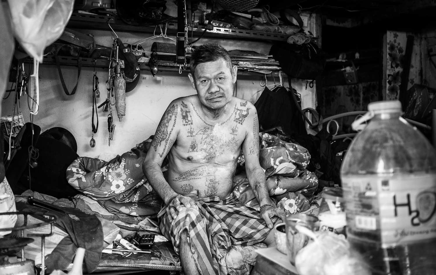 Oude man in zijn hut in Khlongtoey, Bangkok