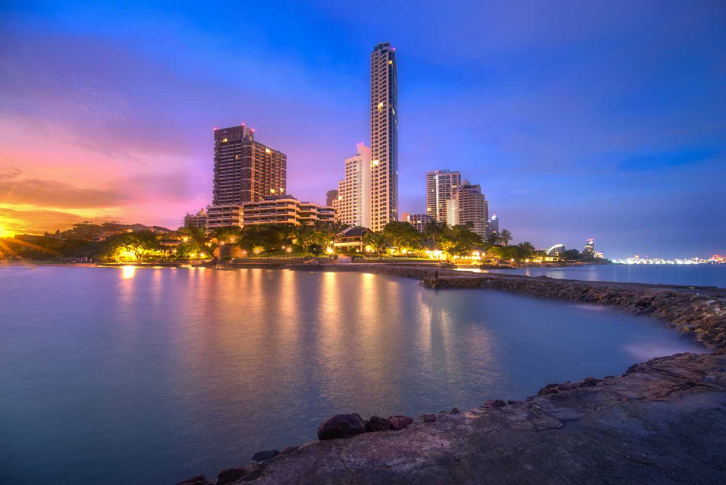 Wong Amat Beach, view from pier of sun and tall buildings