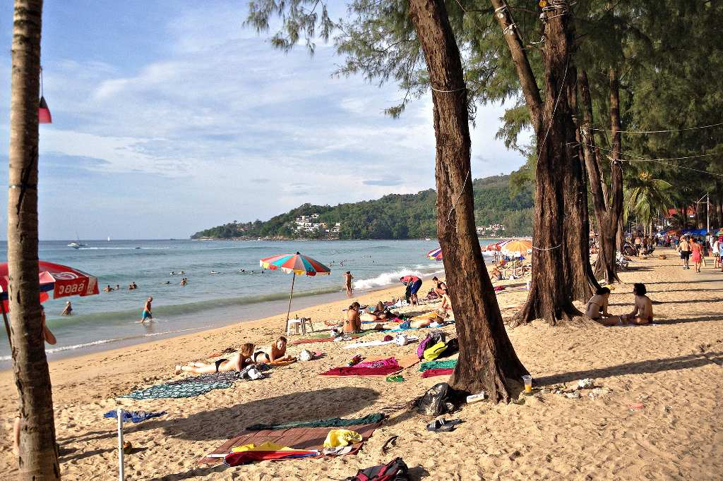Sunbathing in the sand under the shady spots under the trees at Kamala Beach, Phuket