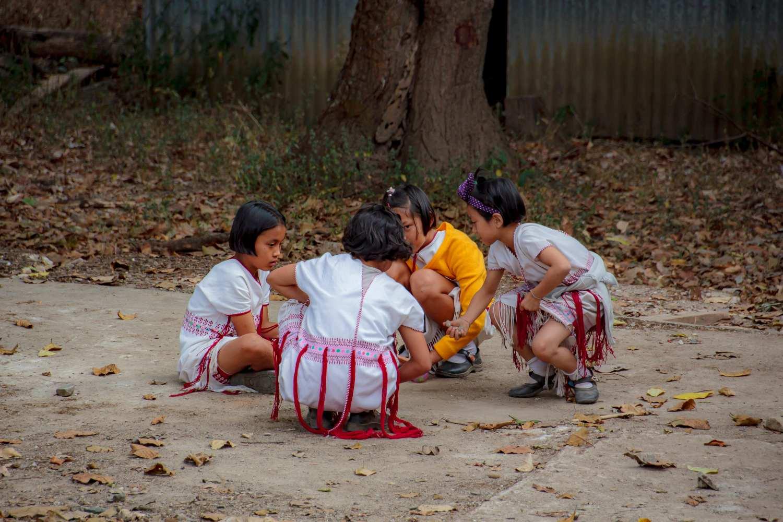 Karen schoolgirls play with pebbles on the playground of their schoolyard in Umpang, Thailand