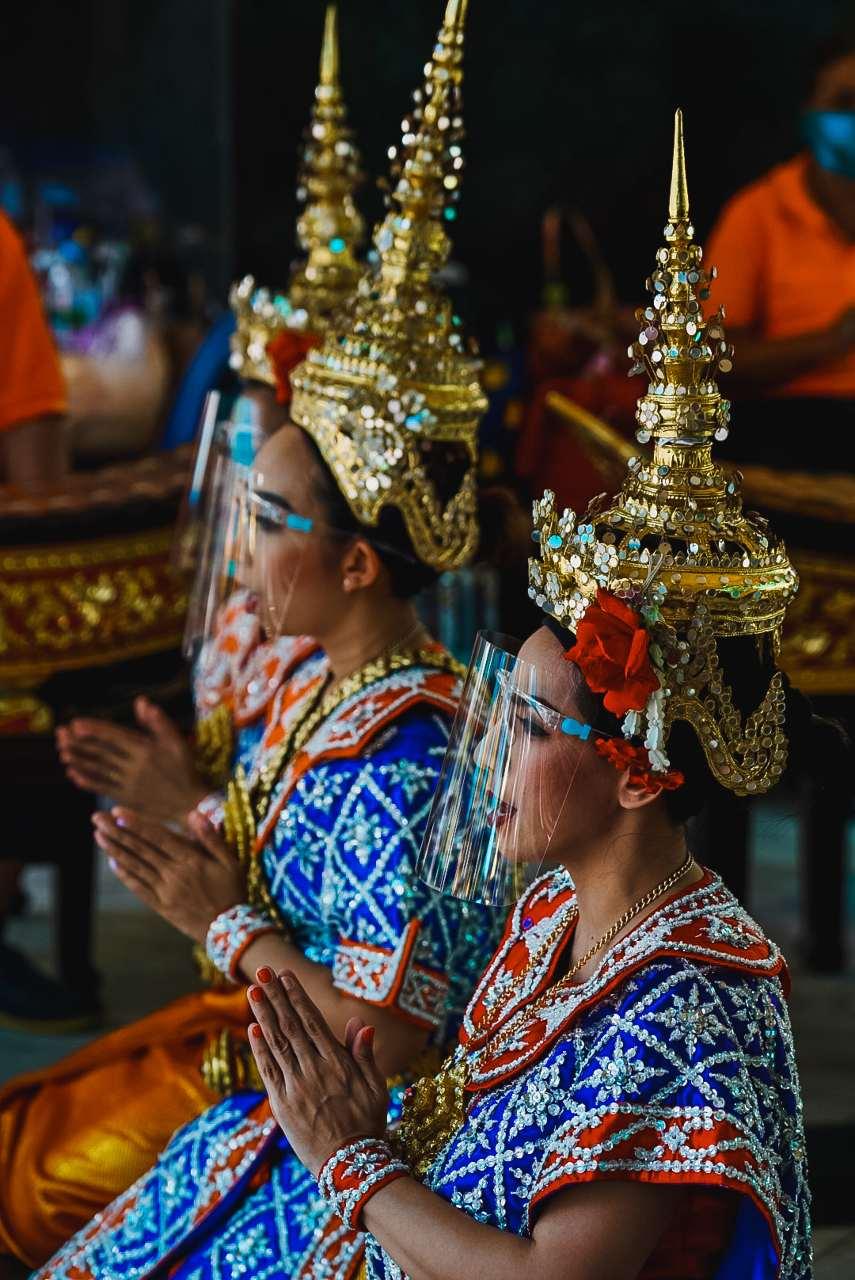 Thai dancers with splash screens against Covid-19 at the Erawan Shrine in Bangkok, Thailand
