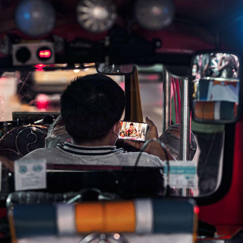 Tuk Tuk bestuurder in Bangkok die op zijn telefoon kijkt