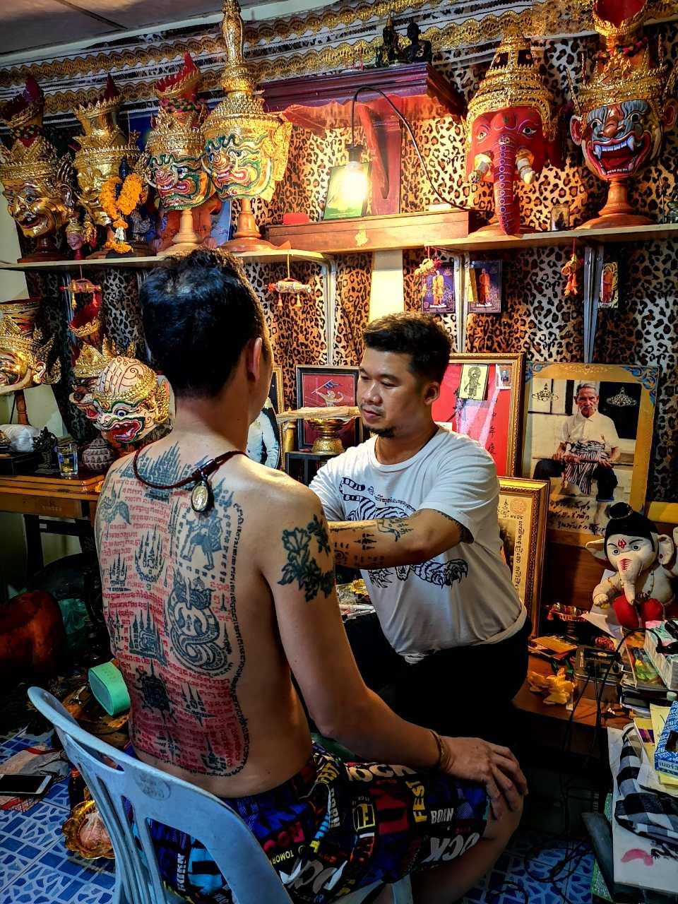 Iemand die een tattoo krijg in Klong Thoey een wijk in Bangkok