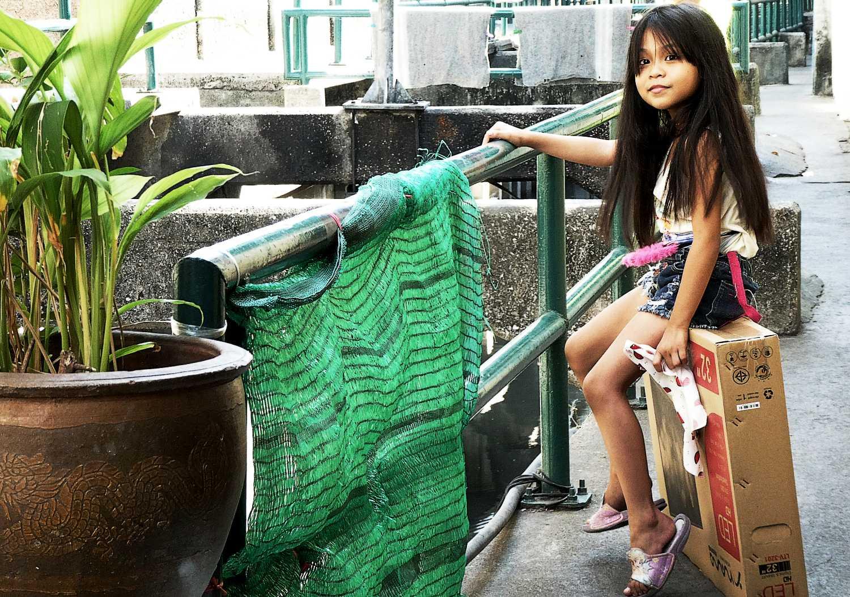 Een klein meisje in Klong Thoey, een wijk in Bangkok