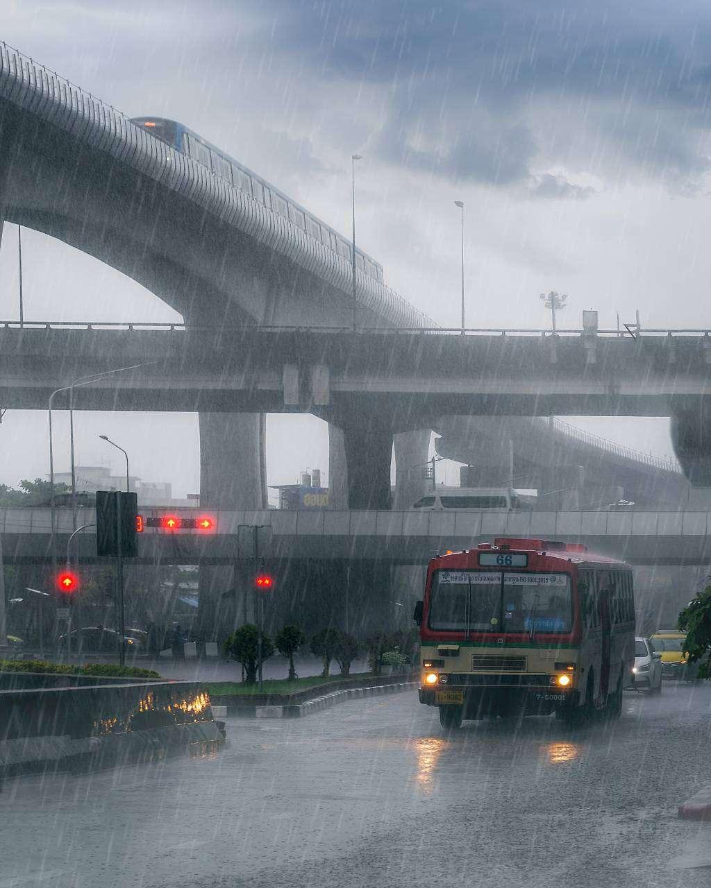 Regen in Bangkok terwijl er een bus over straat rijdt