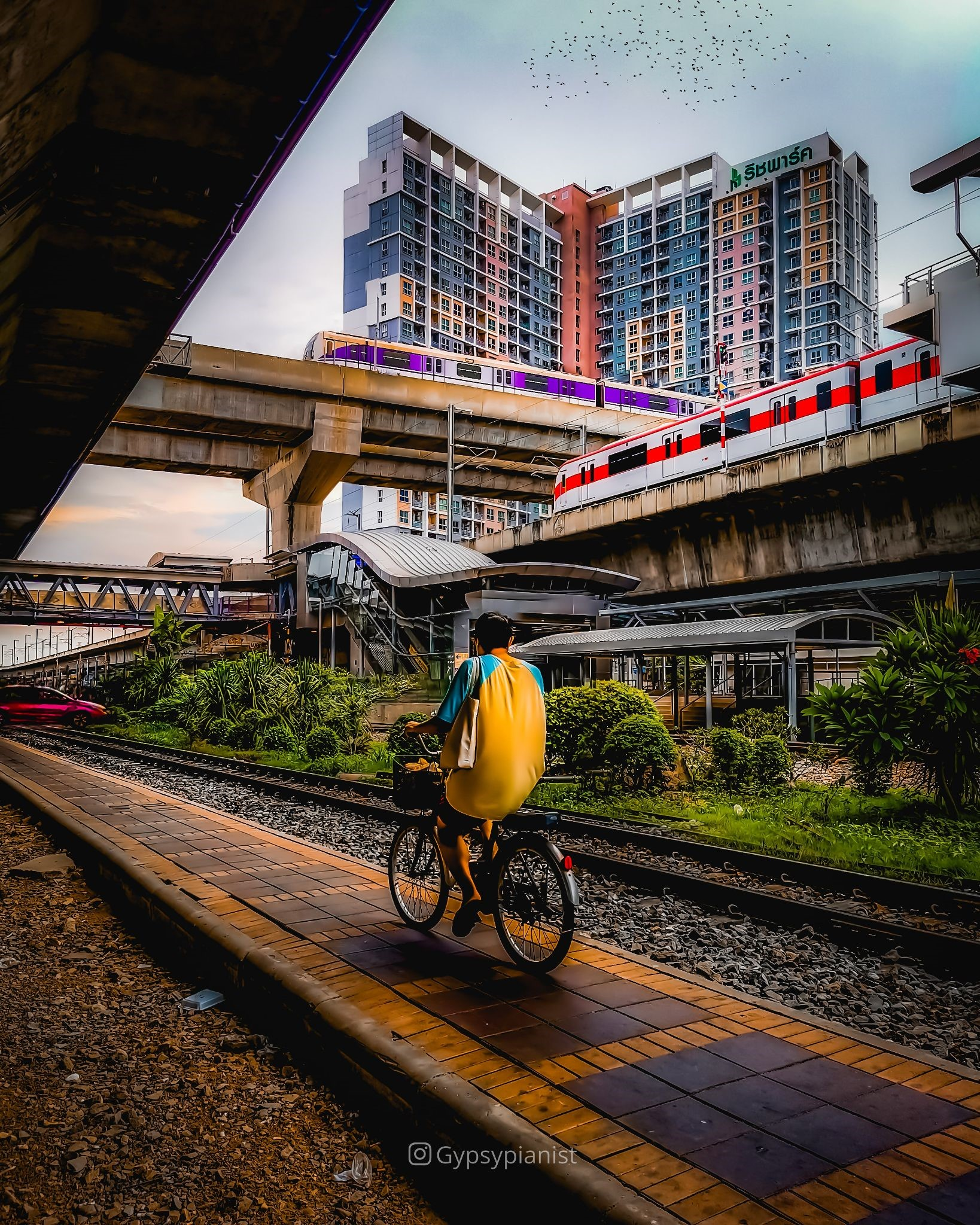 A cyclist in Bangkok while two BTS trains cross each other