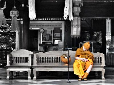A Buddhist Monk On A Bench At The Wat Phra That Doi Suthep In Chiang Mai