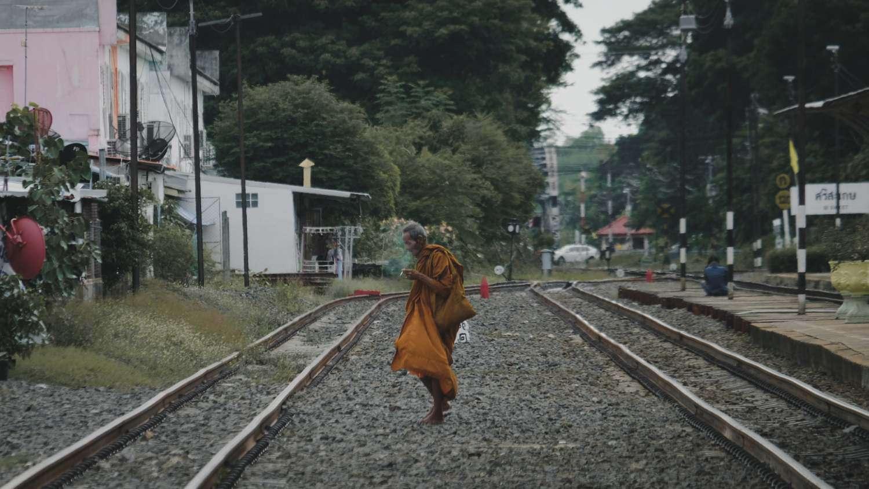 Boeddhistische monnik op het spoor in Sisaket, Thailand