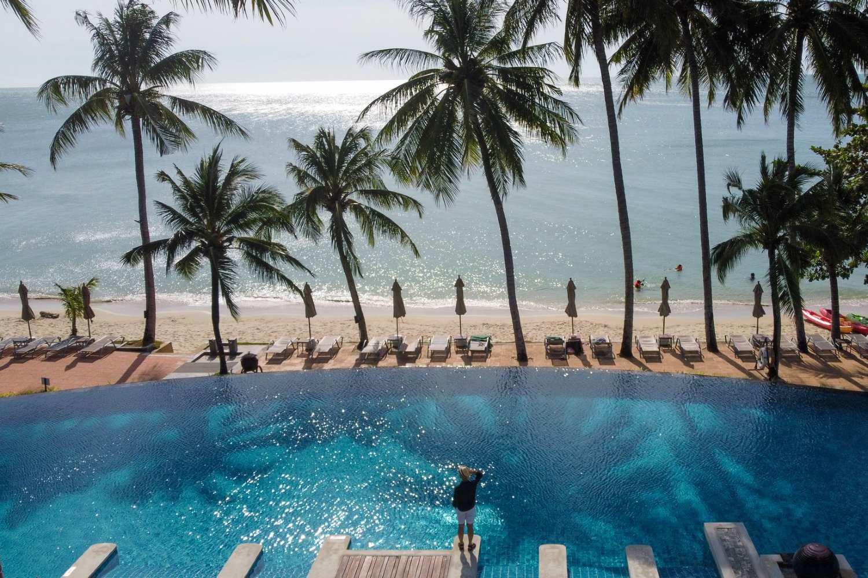 Zwembad met uitzicht op het strand en zee en tropische palmbomen