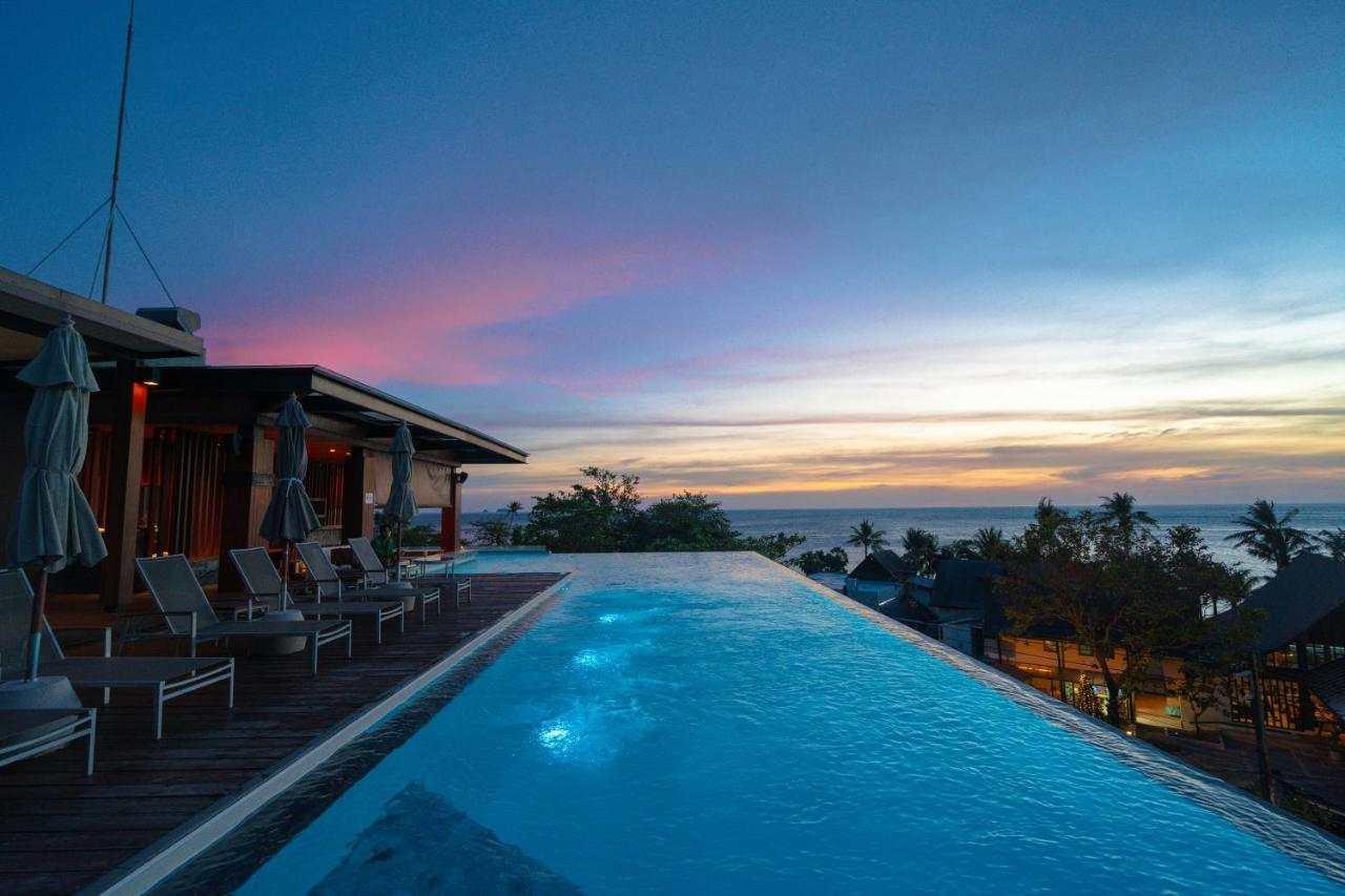 Zwembad op het dak van het hotel met uitzicht op de zee en zonsondergang