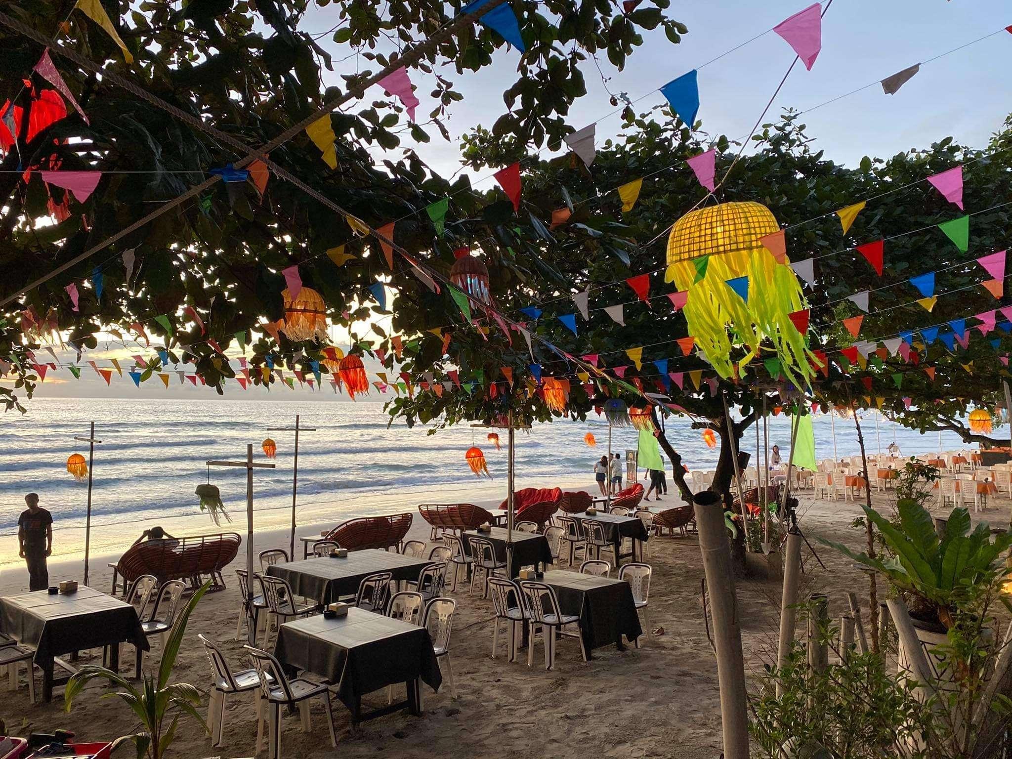 Sabay Bar, tafeltjes onder de verlichte bomen op het strand